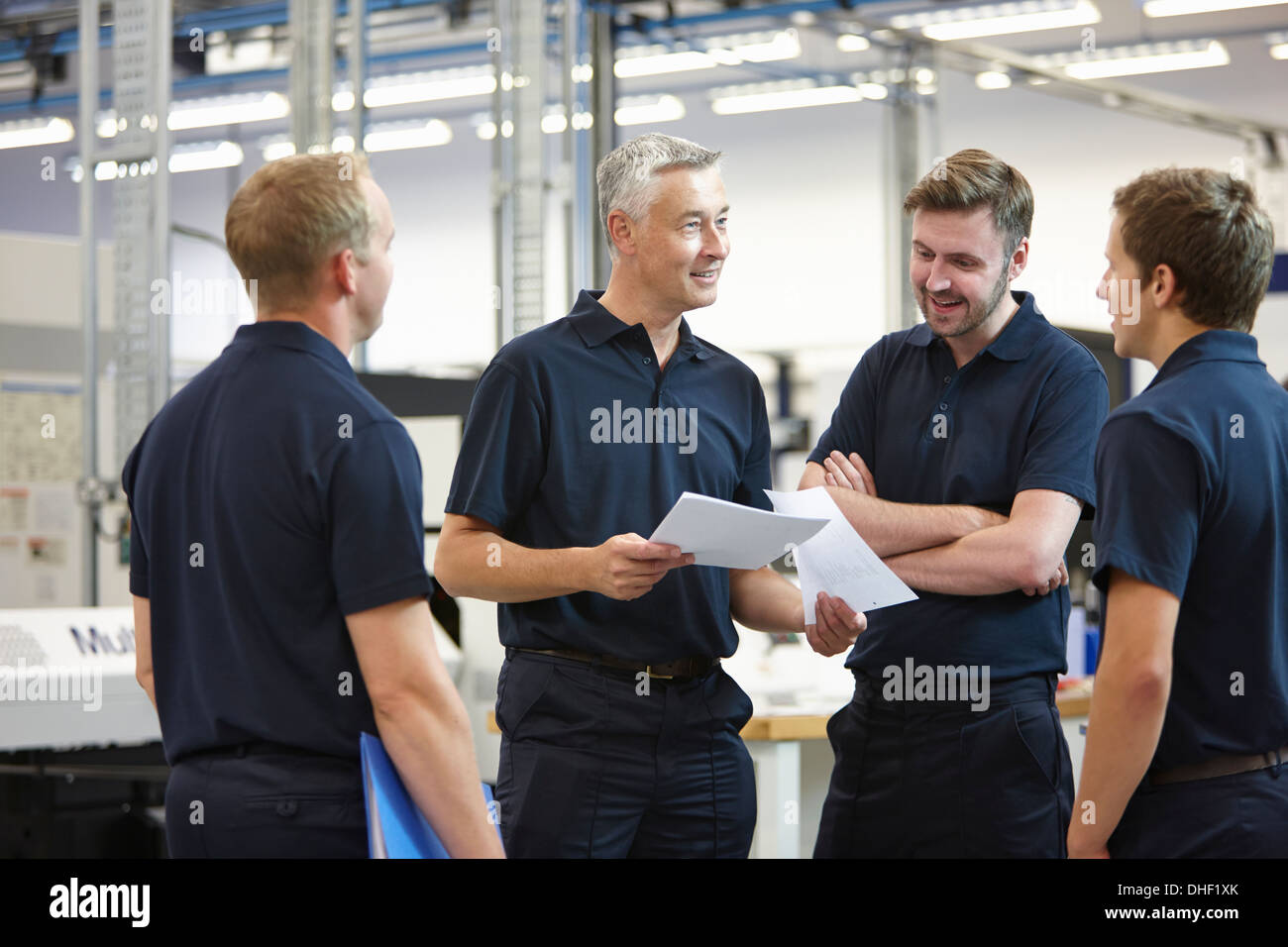 Manager and workers discussing paperwork in engineering factory Stock Photo