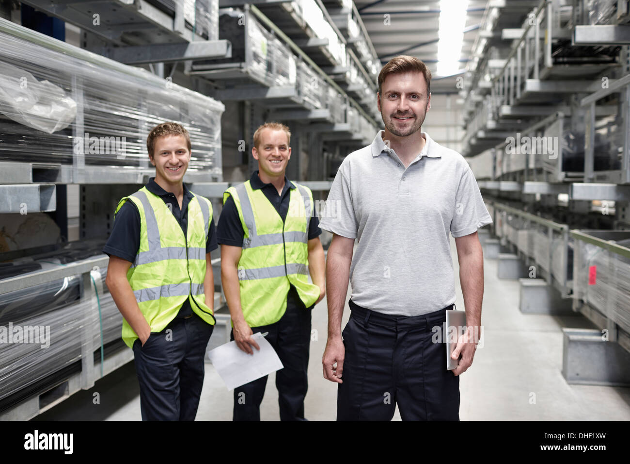 Portrait of three workers in engineering warehouse - Stock Image