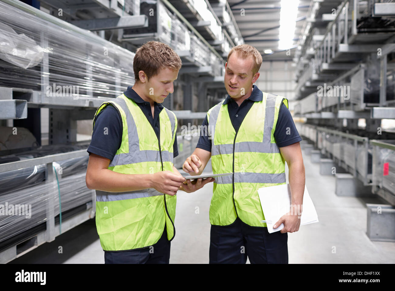 Workers checking orders in engineering warehouse - Stock Image