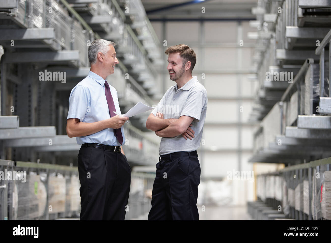 Worker and manager checking orders in engineering warehouse - Stock Image