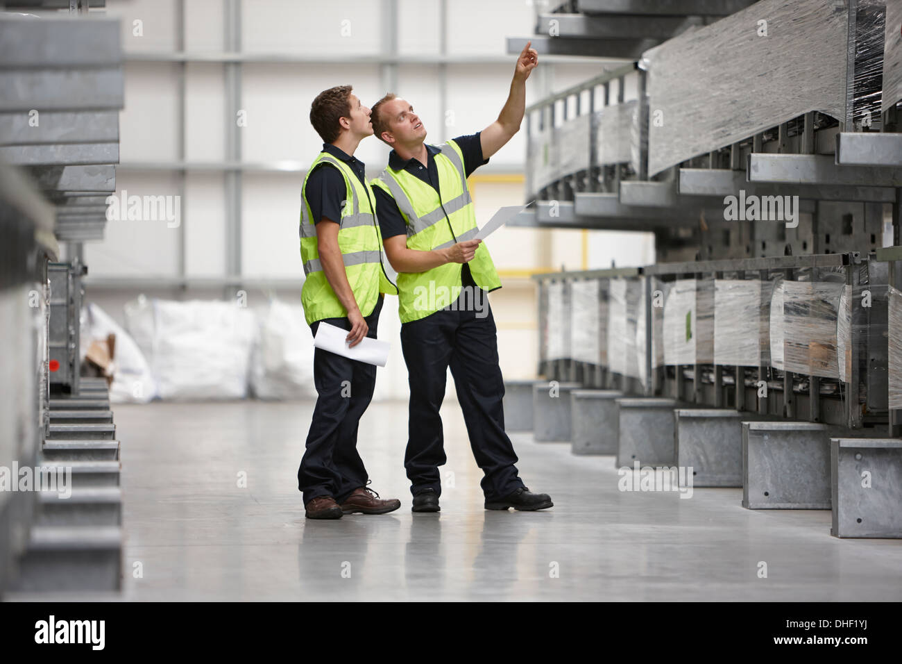 Warehouse workers checking shelves in engineering warehouse - Stock Image