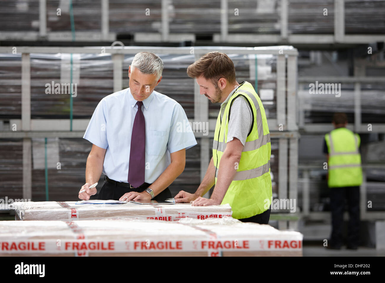 Warehouse worker and manager checking order in engineering warehouse - Stock Image