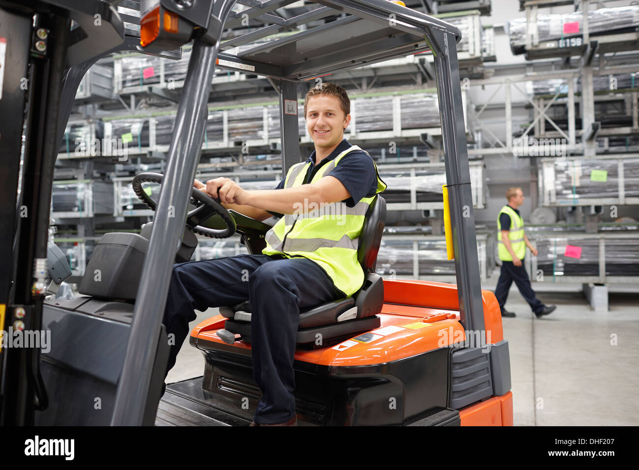 Forklift truck driver in engineering warehouse - Stock Image