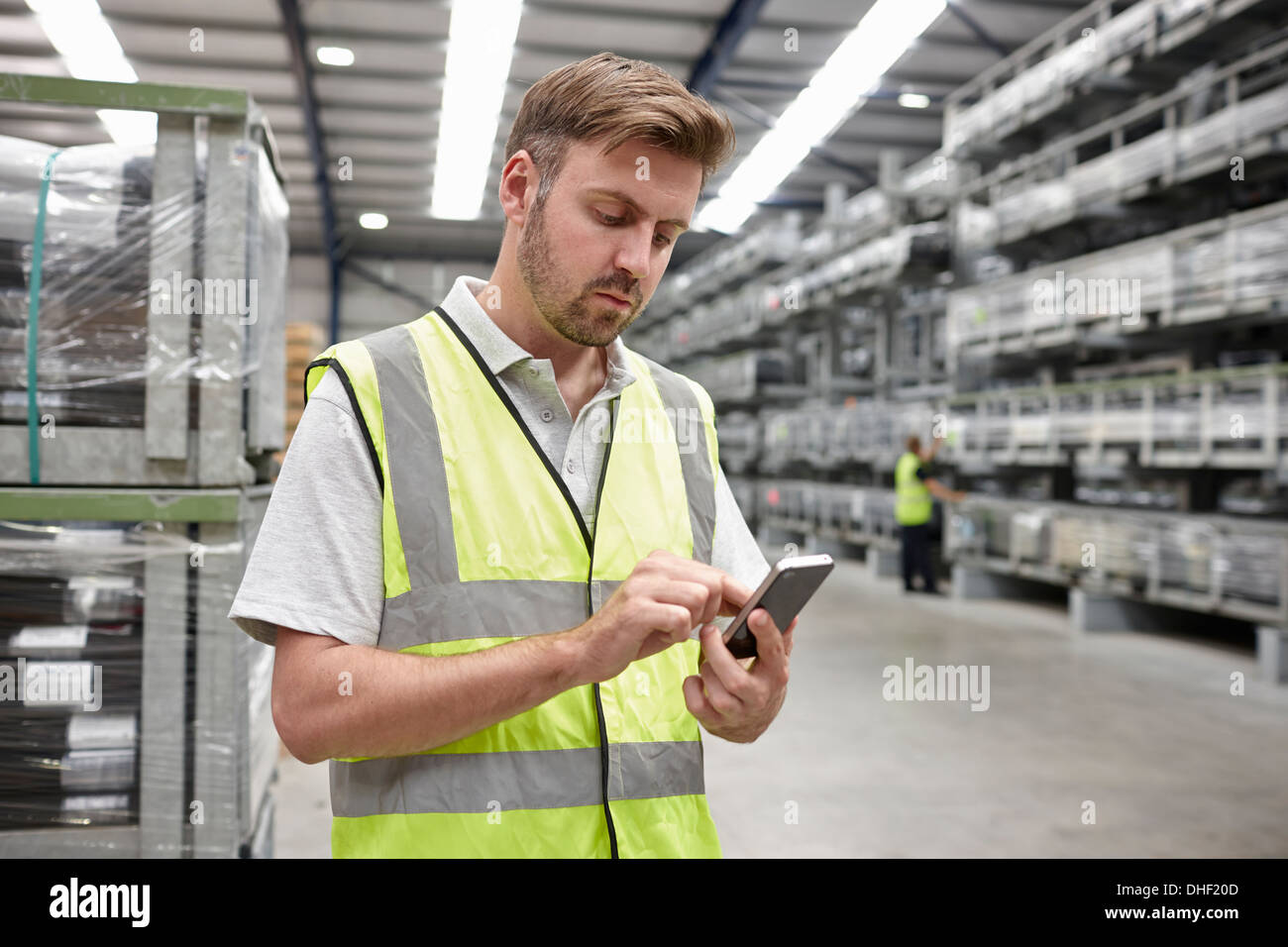 Portrait of worker using mobile phone in engineering warehouse - Stock Image