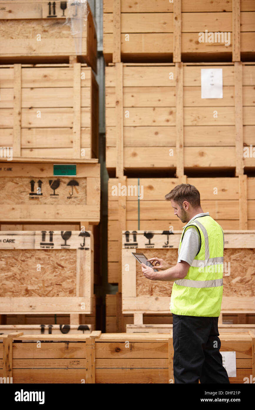 Warehouse worker checking crates in engineering warehouse - Stock Image