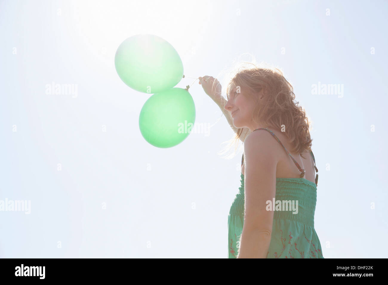 Woman holding two green balloons, Wales, UK - Stock Image