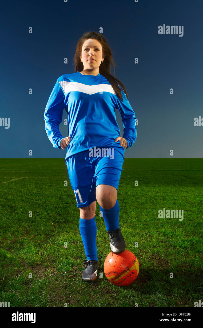 Portrait of female footballer with foot on ball - Stock Image