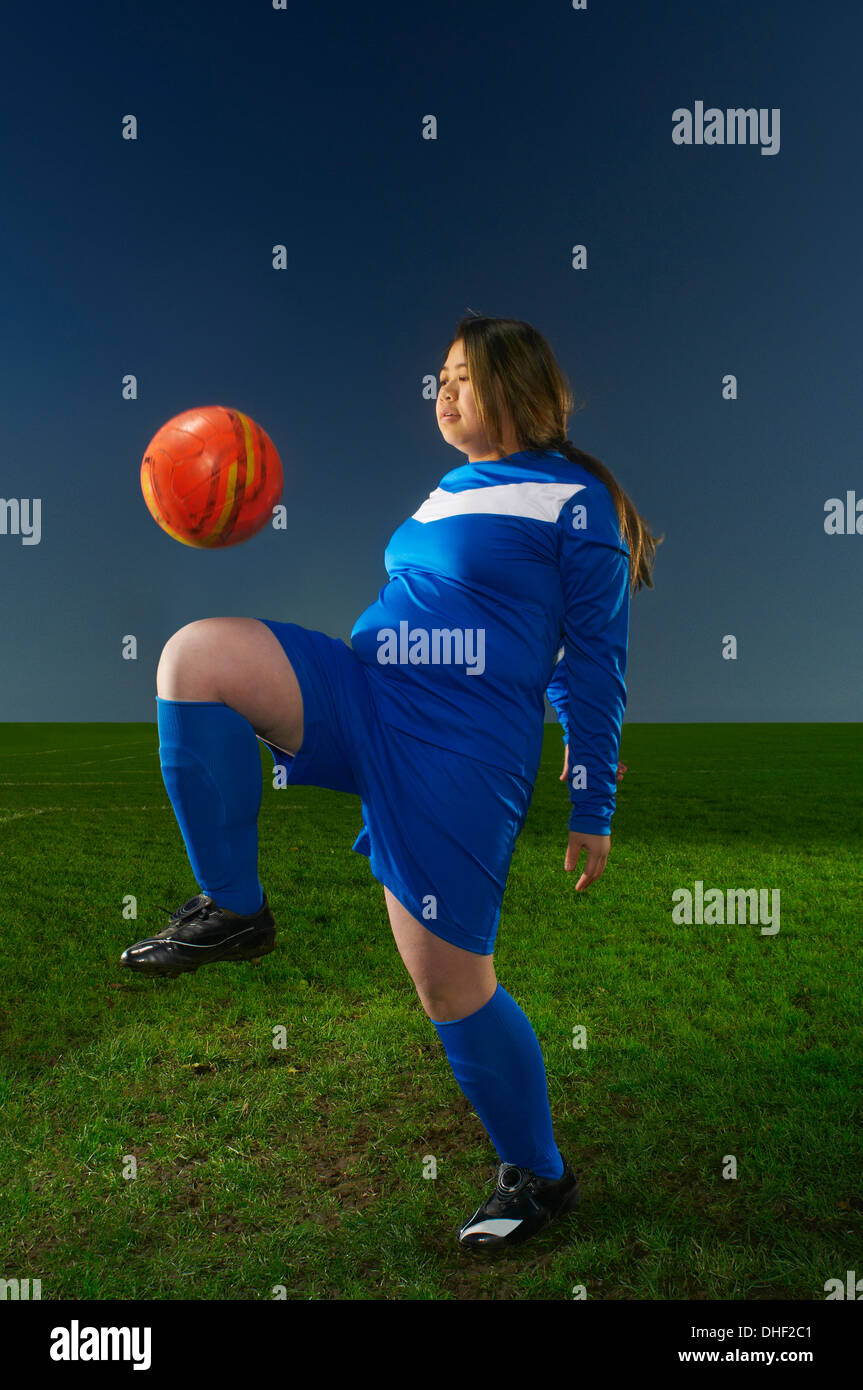 Female footballer playing keepy uppy with ball - Stock Image