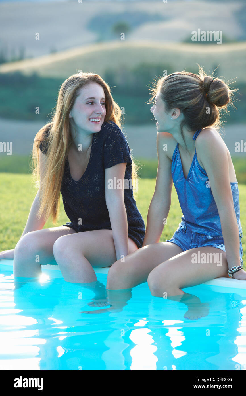 Two Teenage Girls Sitting At Poolside Tuscany Italy