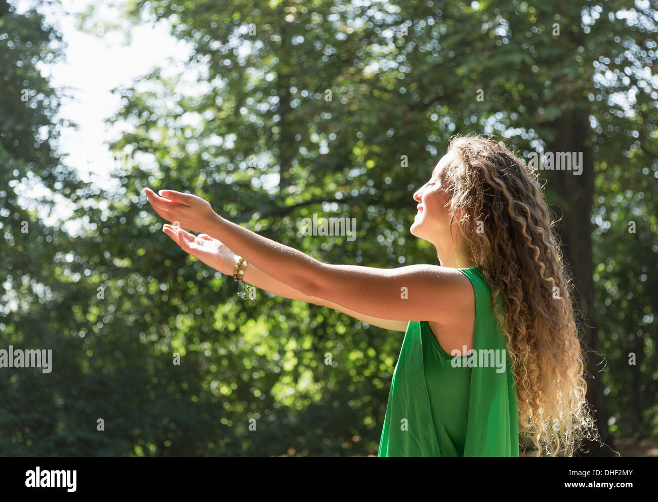 Teenage girl wearing green top with arms out, Prague, Czech Republic - Stock Image