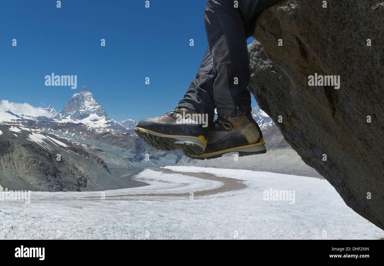 Man sitting on rock by the Matterhorn, Zermatt, Canton Wallis, Switzerland - Stock Image