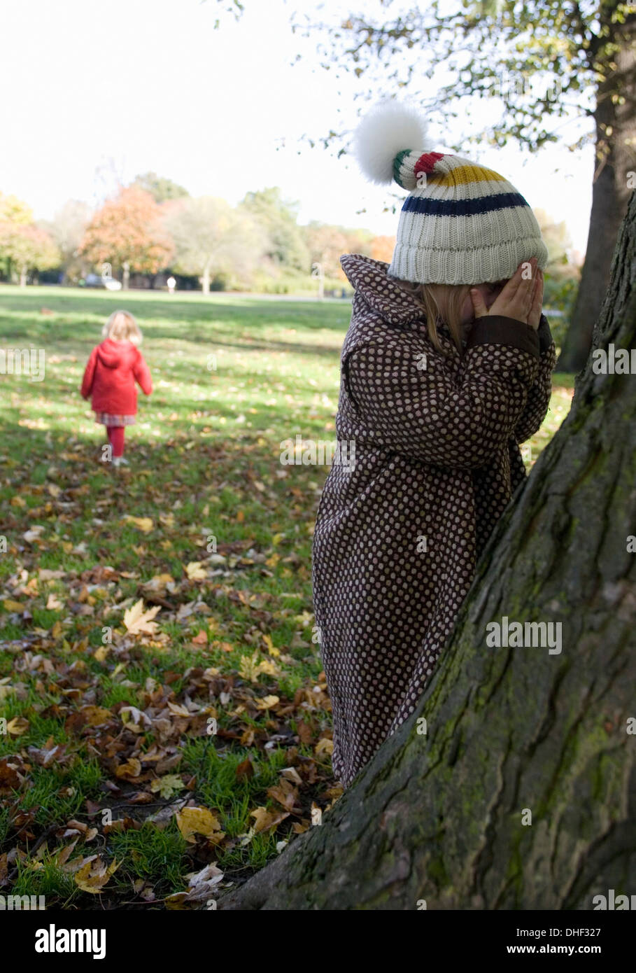 Girls playing hide and seek in park, London, England, UK - Stock Image