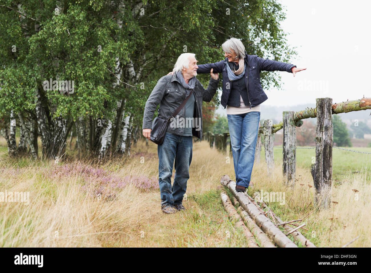 Senior couple, woman balancing on logs - Stock Image