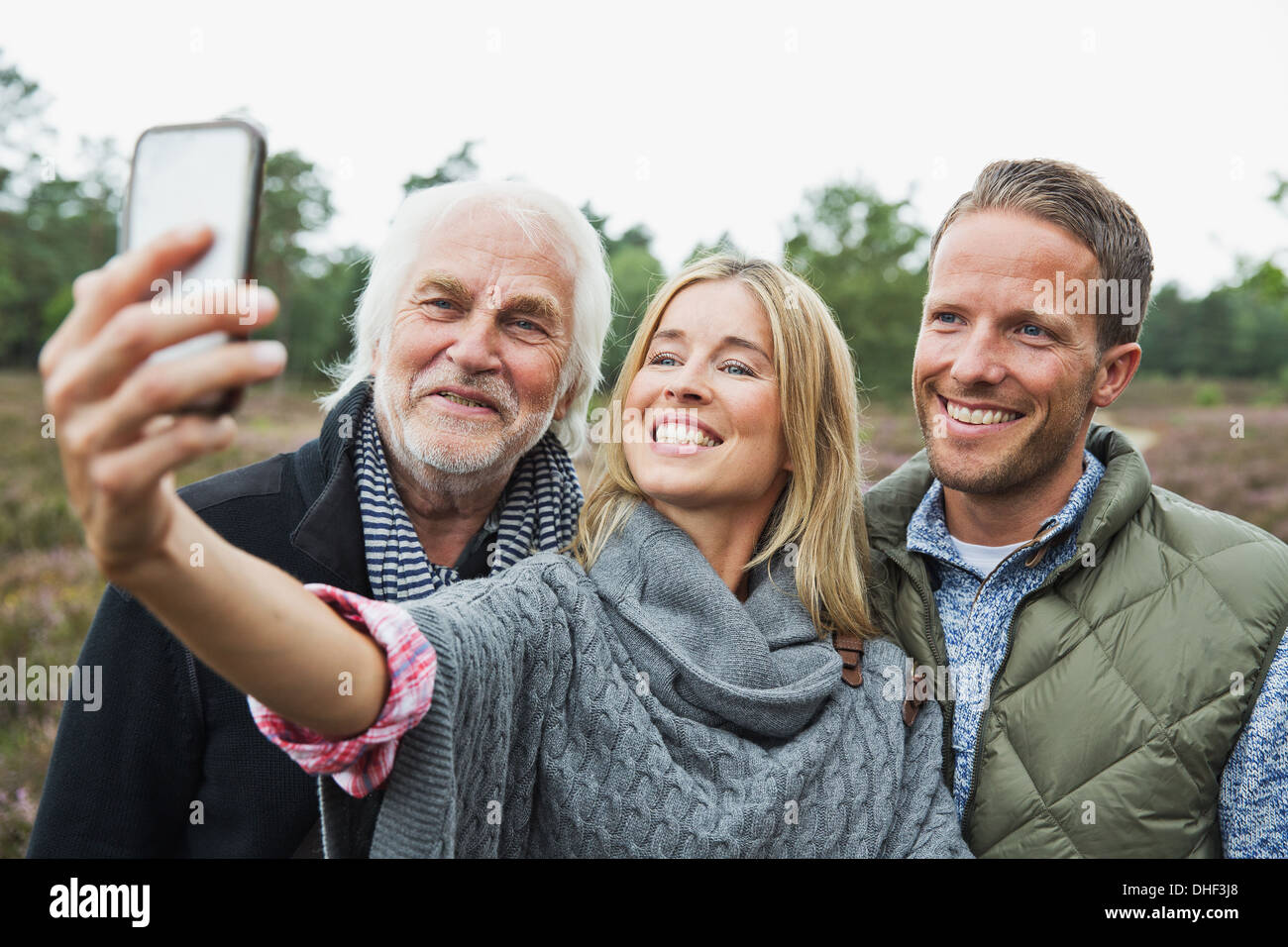 Mid adult woman taking photograph with camera phone - Stock Image