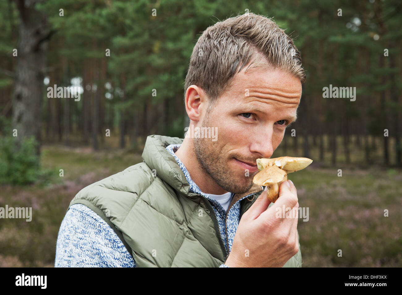 Mid adult man smelling mushroom - Stock Image