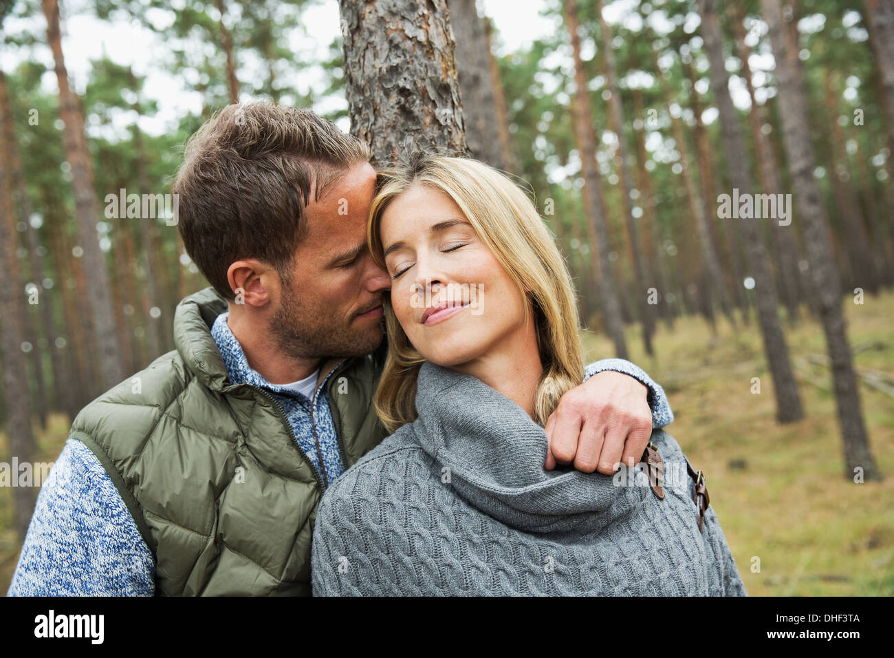 Mid adult couple hugging in forest Stock Photo
