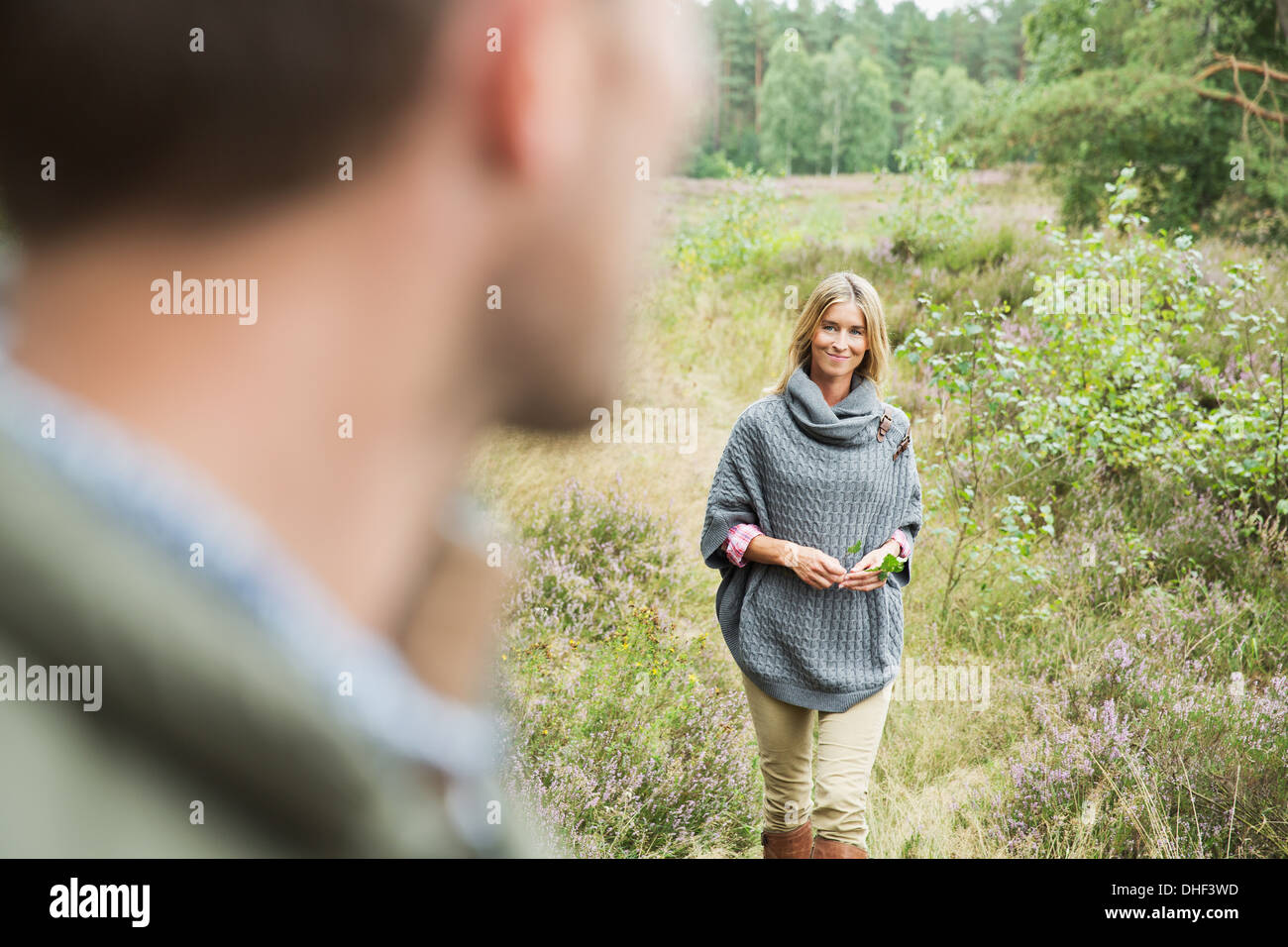 Mid adult woman holding leaf, man blurred in foreground - Stock Image