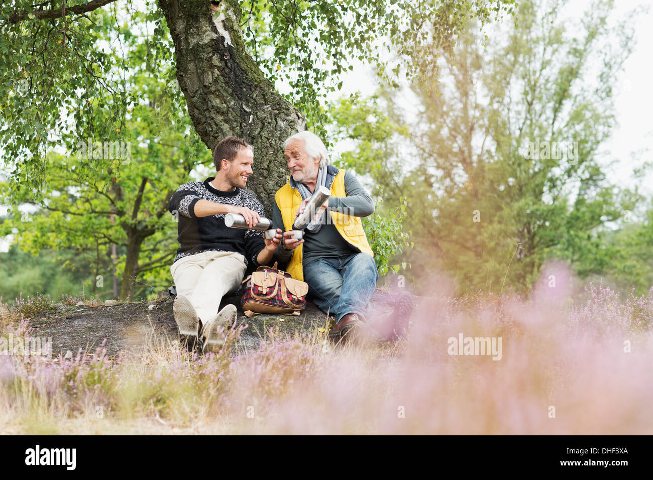 Father and adult son drinking coffee from flask - Stock Image