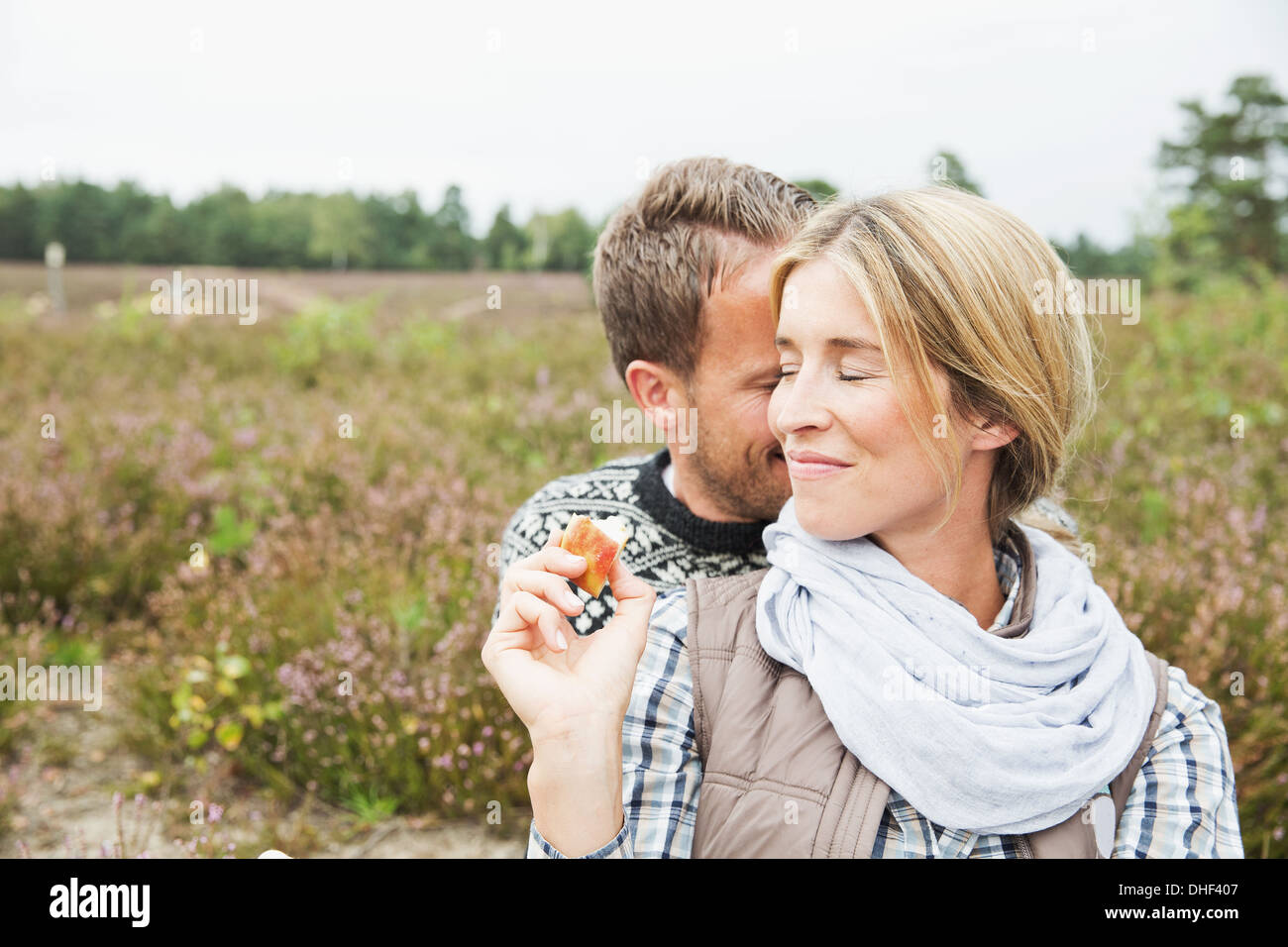 Mid adult couple, woman smiling with eyes closed - Stock Image