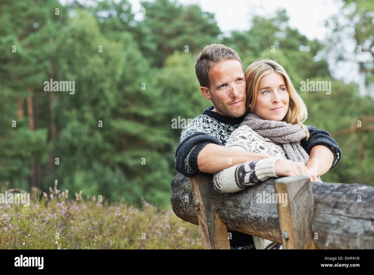 Mid adult couple on bench looking away - Stock Image