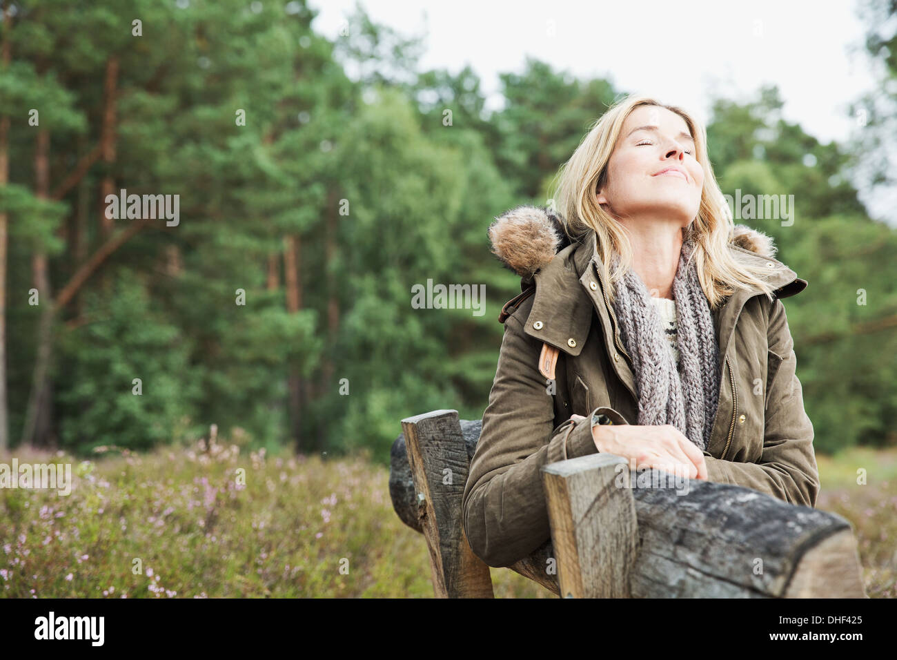 Mid adult woman on bench with eyes closed - Stock Image