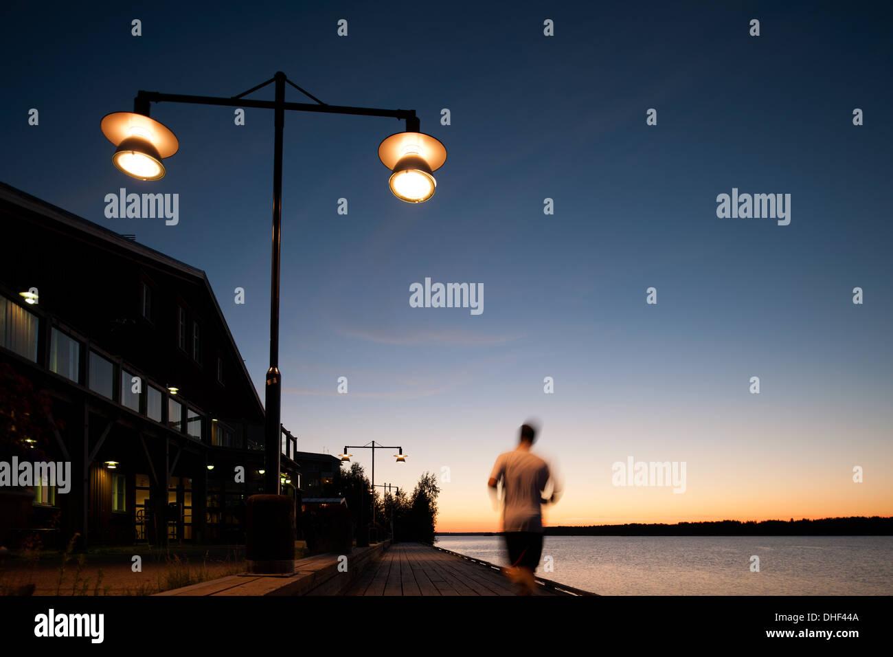 Man jogging on waterfront, Lulea, Sweden - Stock Image