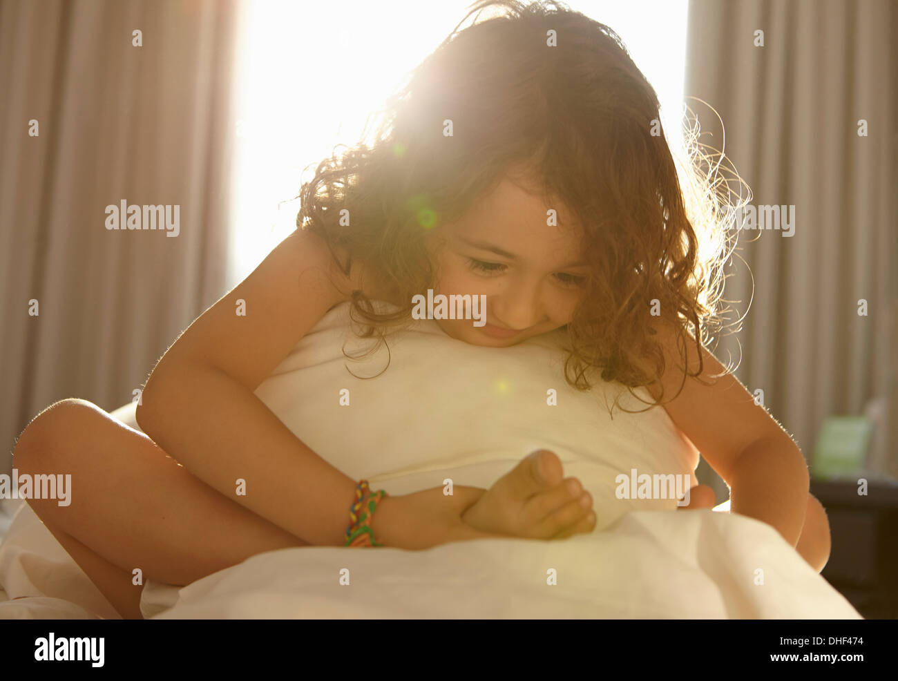 Girl on bed holding foot - Stock Image