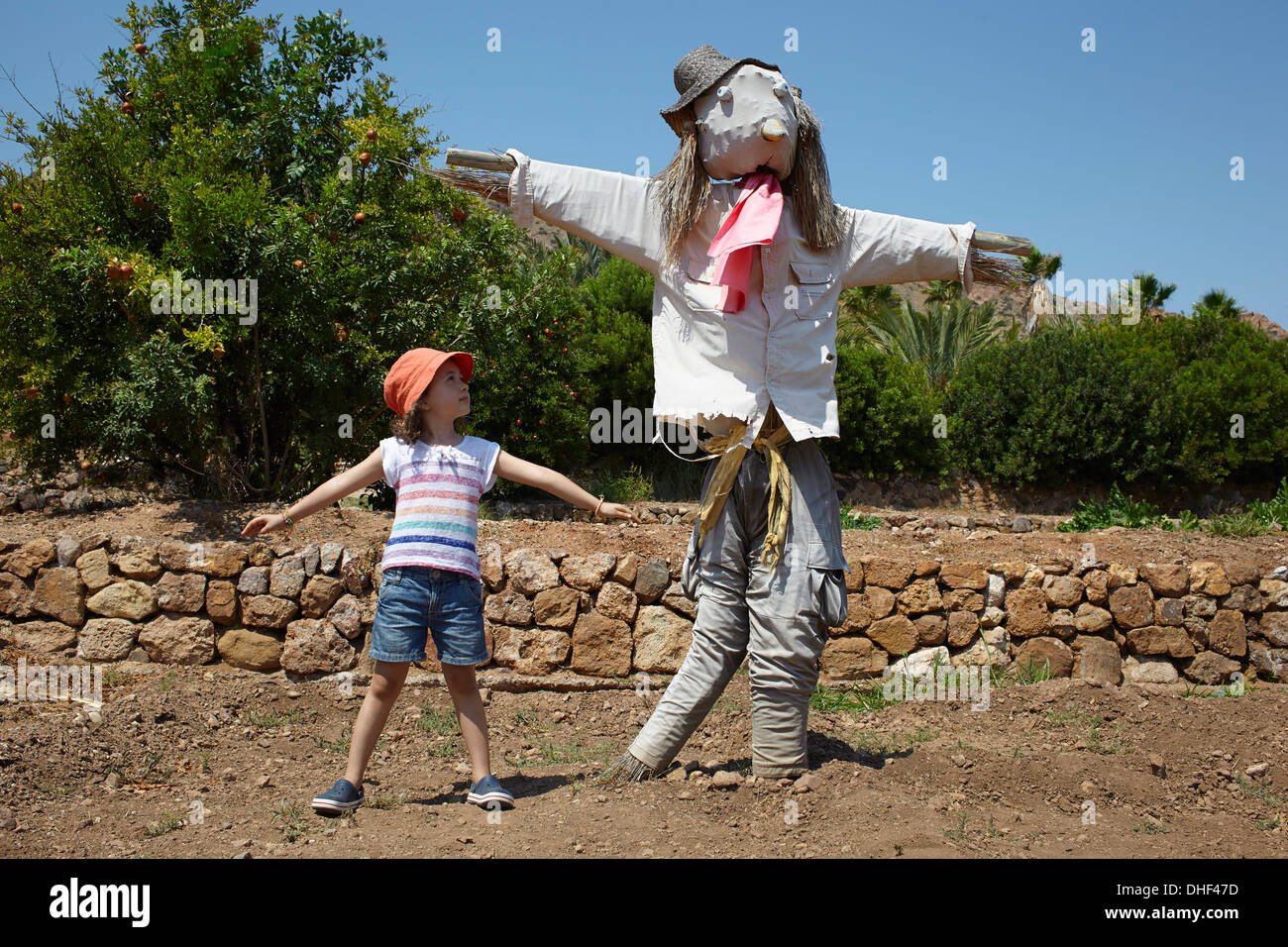 Girl standing next to scarecrow with arms out - Stock Image