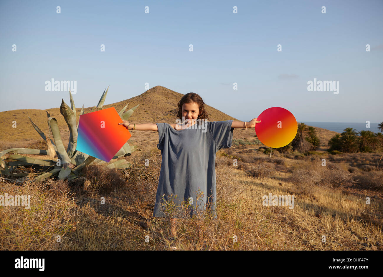 Girl holding bright shapes in desert, Cabo de Gata, Almeria, Spain - Stock Image