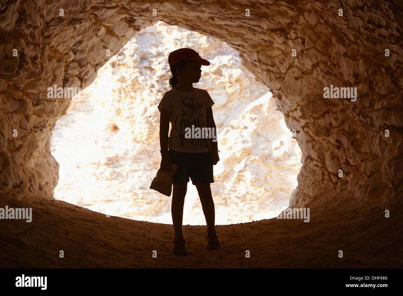 Girl standing in entrance of cave, Cabo de Gata, Almeria, Spain - Stock Image