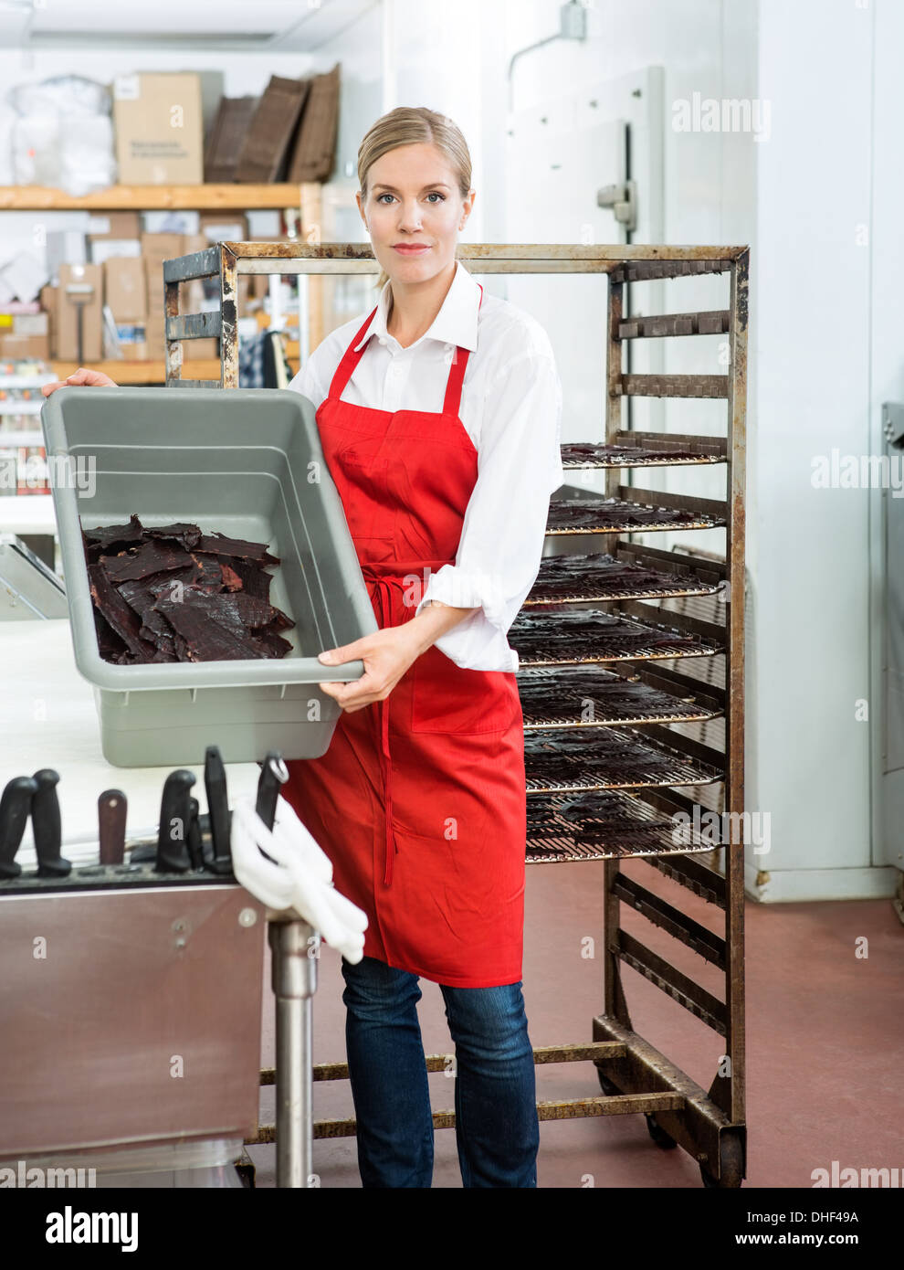 Worker Showing Beef Jerky In Basket At Butcher's Shop Stock Photo