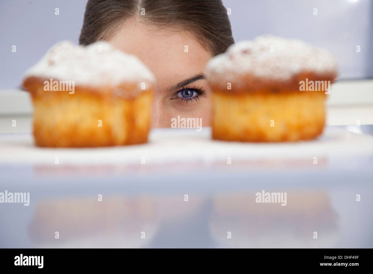 Young woman looking at freshly bakes cakes - Stock Image