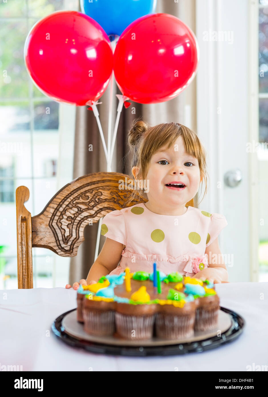 Girl Sitting In Front Of Cake At Home - Stock Image