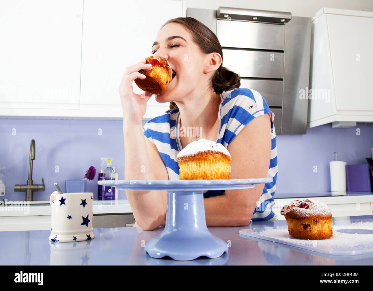 Young woman eating muffin - Stock Image