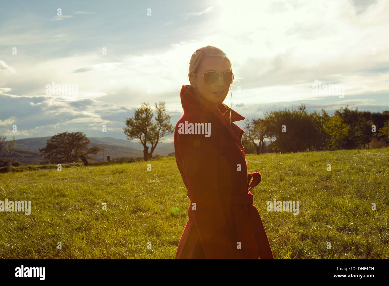 Young woman in field posing in sunglasses - Stock Image