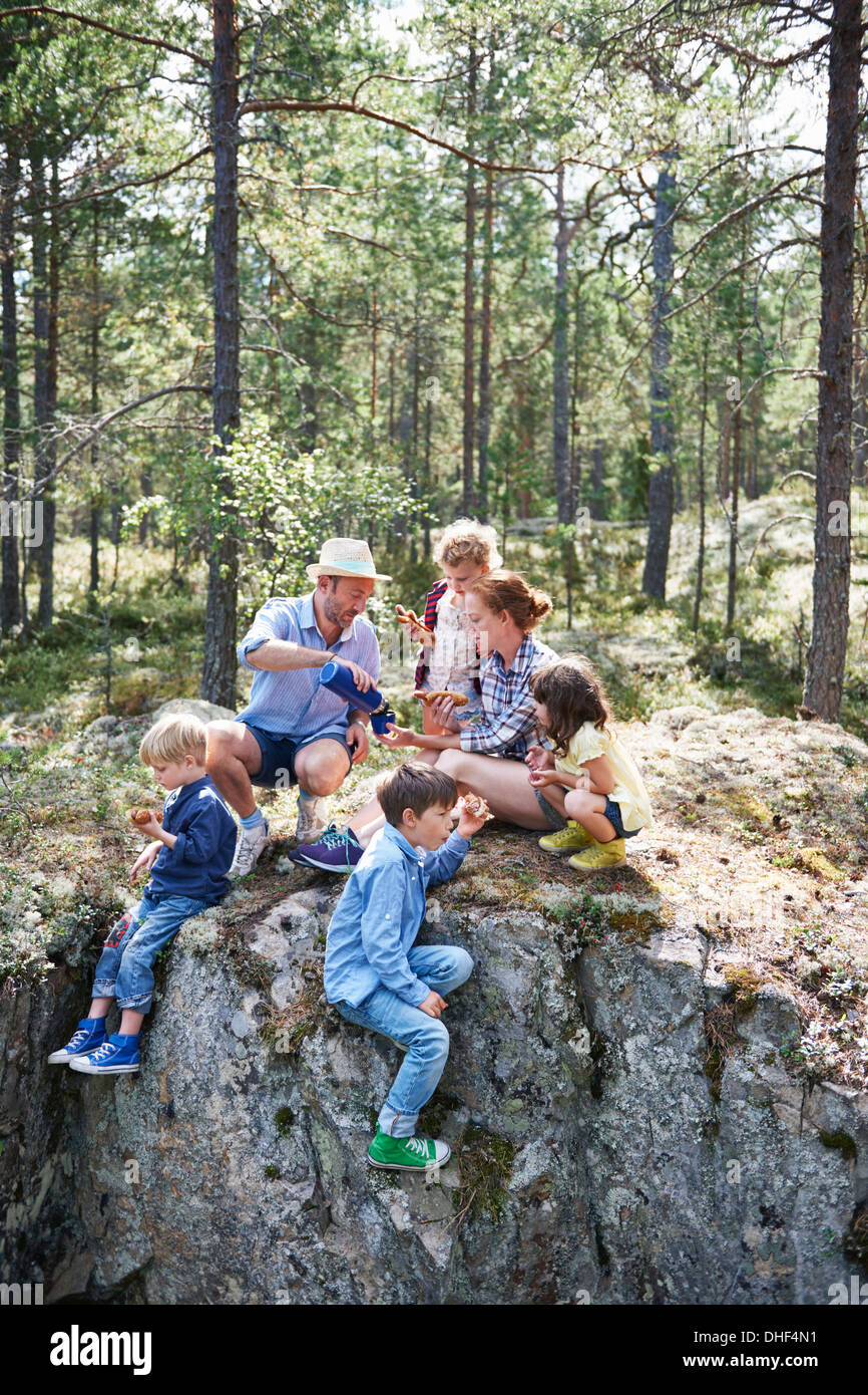 Family sitting on rocks in forest eating picnic - Stock Image