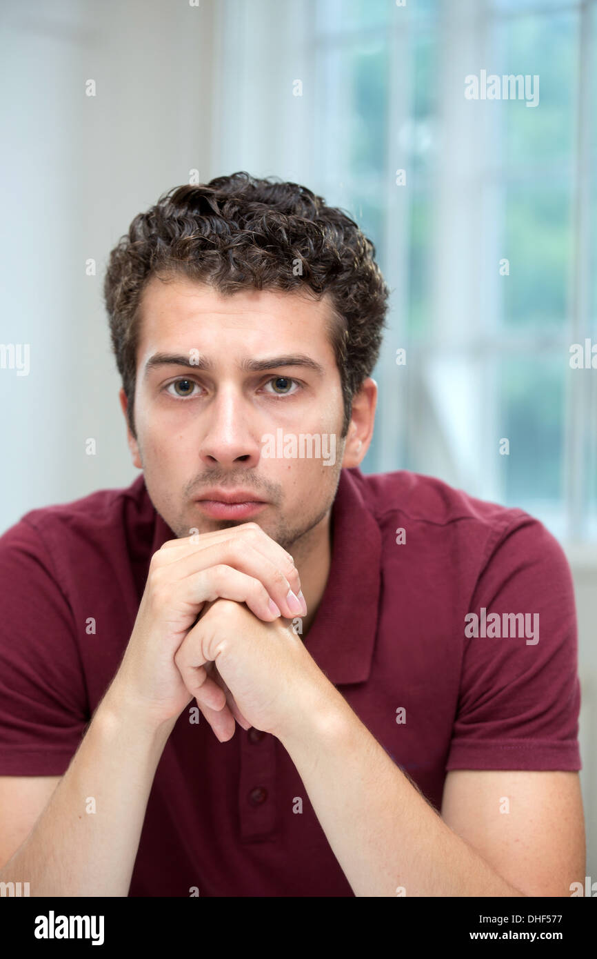 Young man resting chin on clasped hands - Stock Image