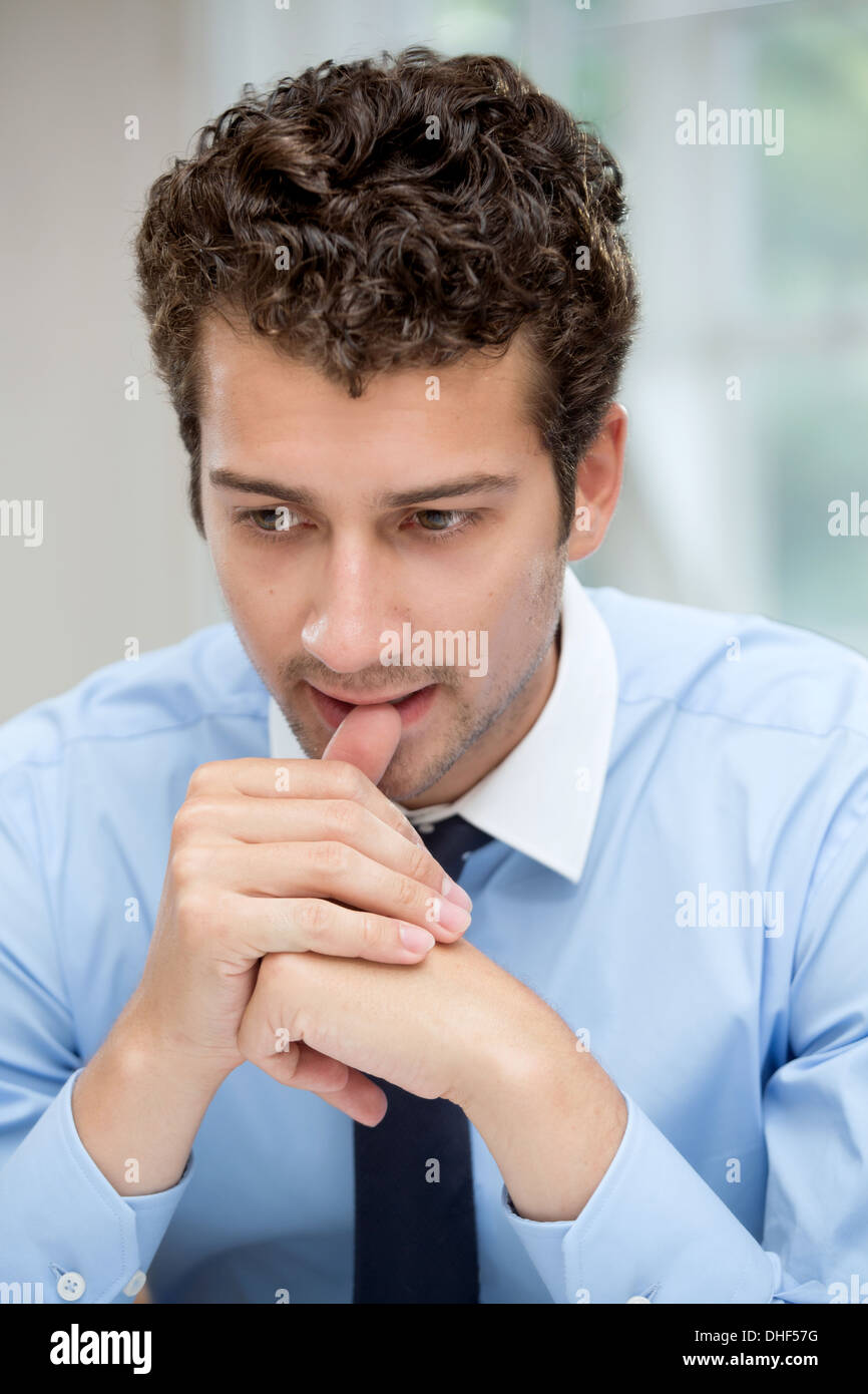 Young man in deep thought - Stock Image