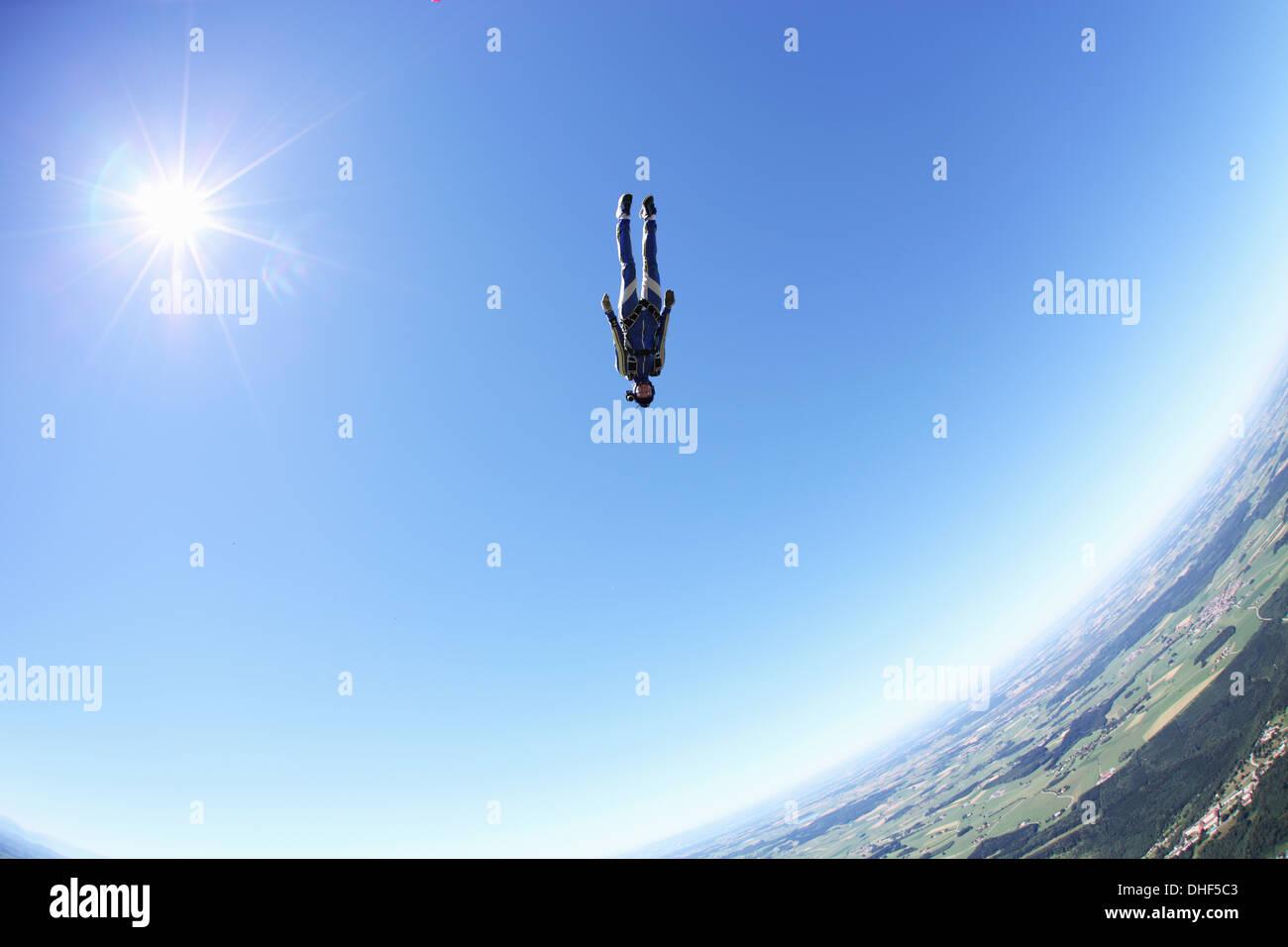 Female skydiver free falling head first above Leutkirch, Bavaria, Germany - Stock Image
