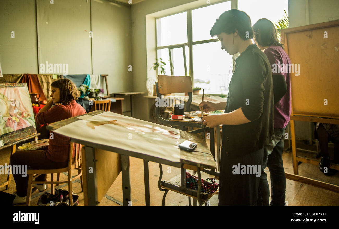 Three young female artists painting in studio - Stock Image
