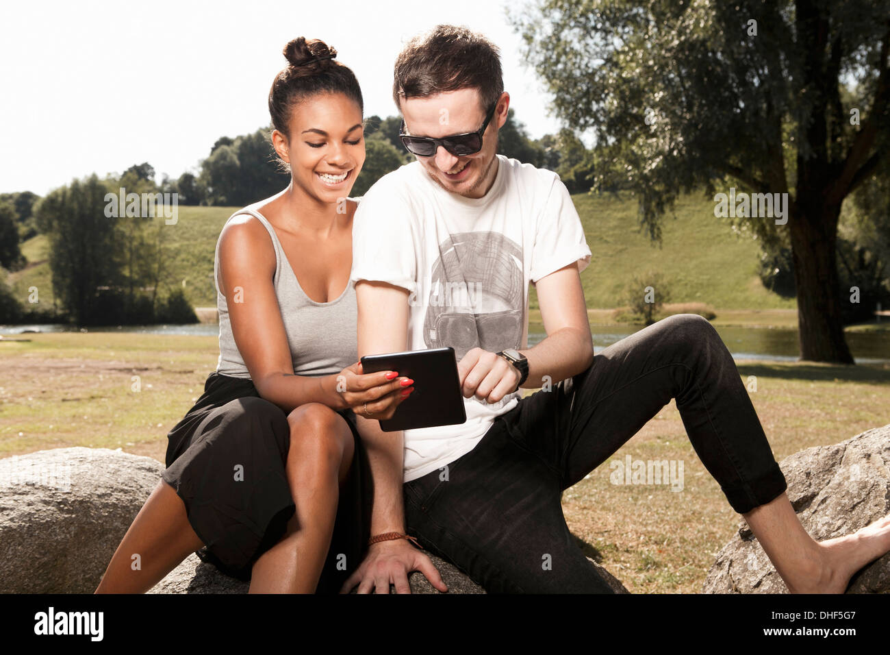 Young couple using digital tablet in park - Stock Image