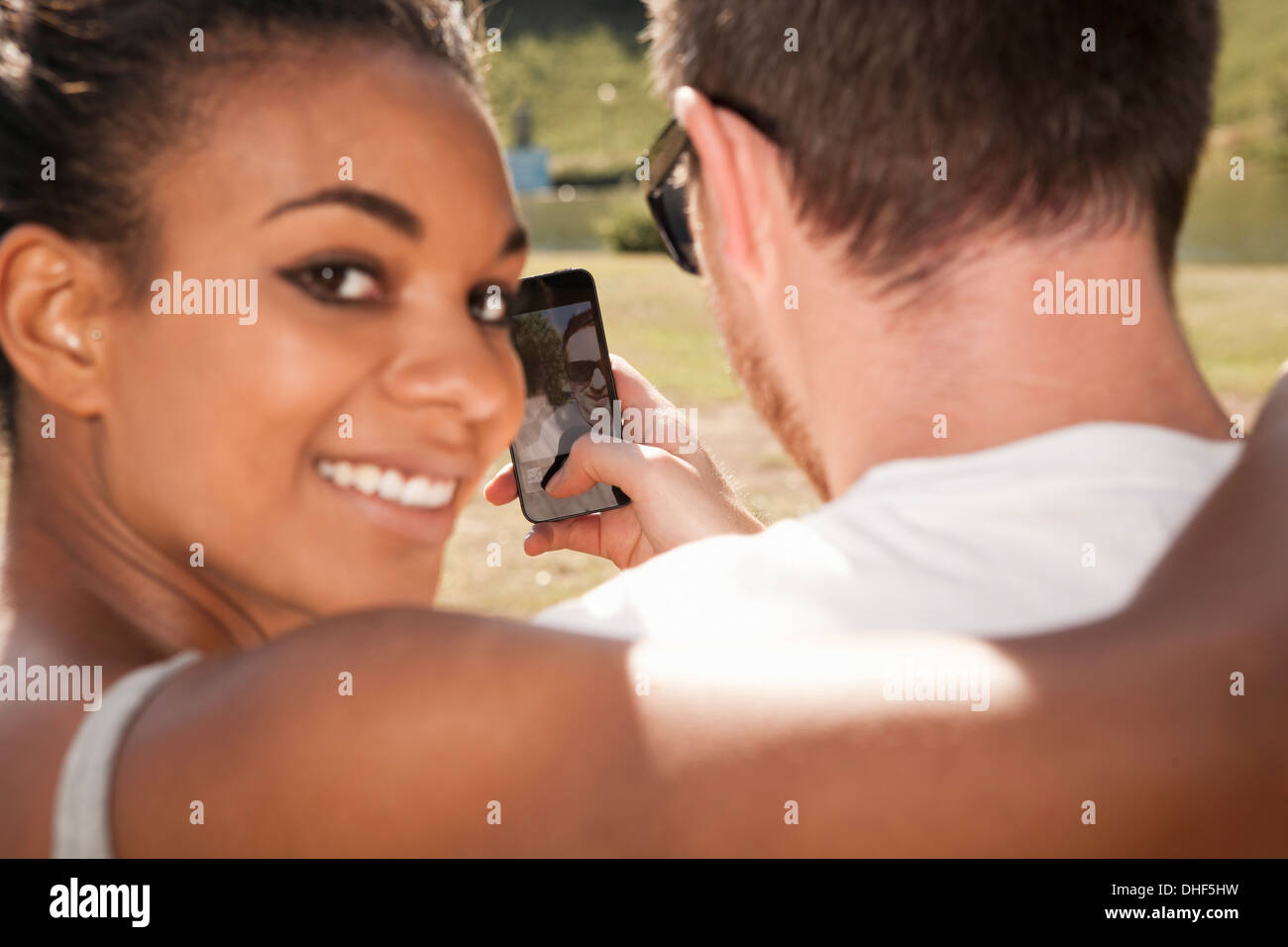 Young couple taking picture of themselves with phone, woman looking over shoulder - Stock Image