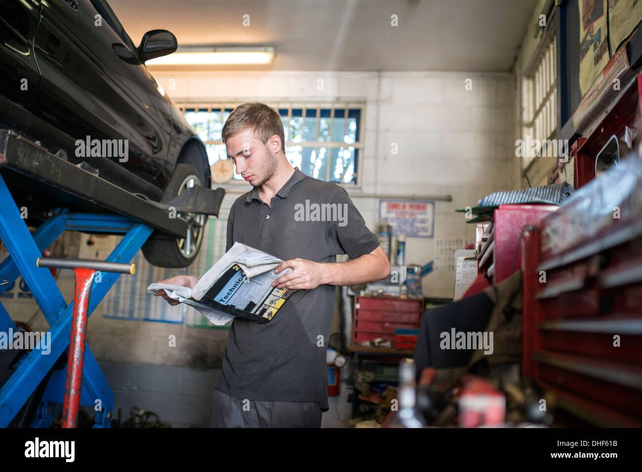 Mechanic reading manual in garage Stock Photo