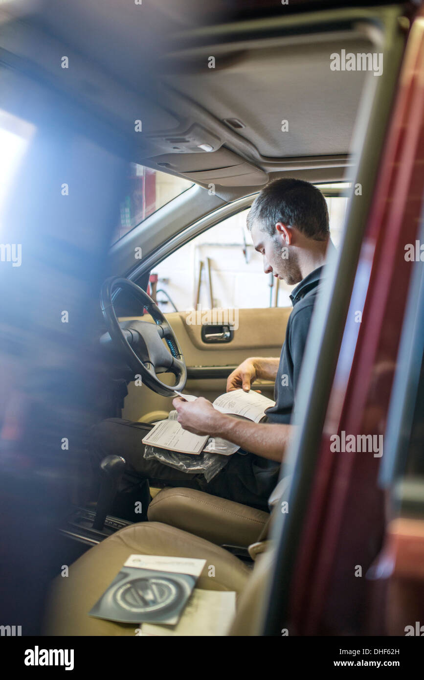Mechanic sitting in driver's seat of car with manual - Stock Image