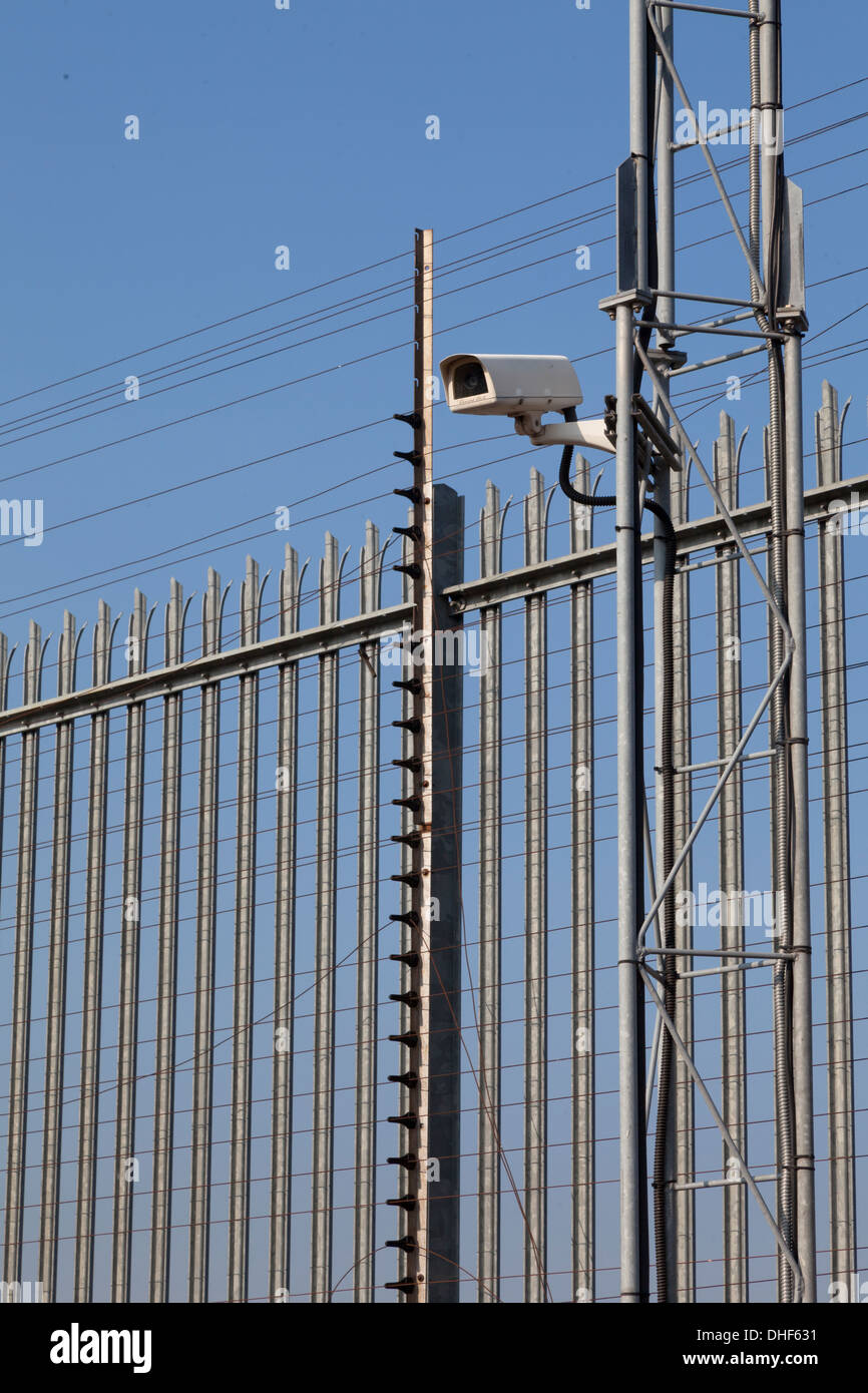 Fence and surveillance video camera - Stock Image