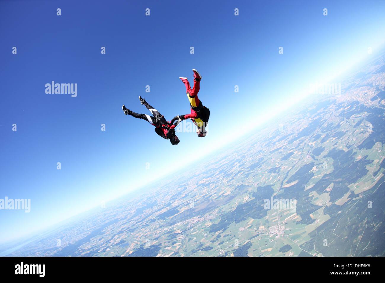 Female skydivers upside down above Leutkirch, Bavaria, Germany - Stock Image