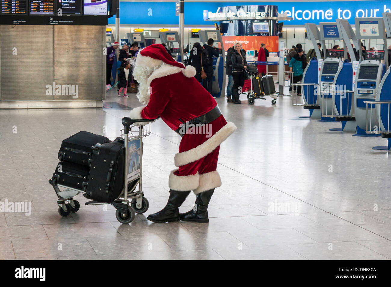 Father Christmas waits at T5 Heathrow Airport, London.  Christmas travel delays concept. - Stock Image