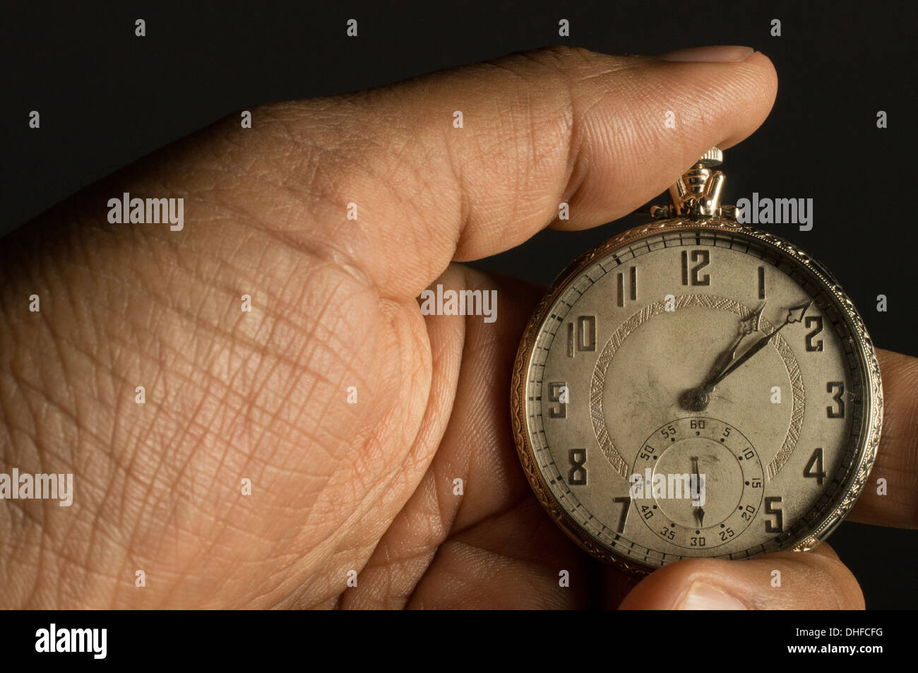 An African American hand holding an antique pocket watch - Stock Image