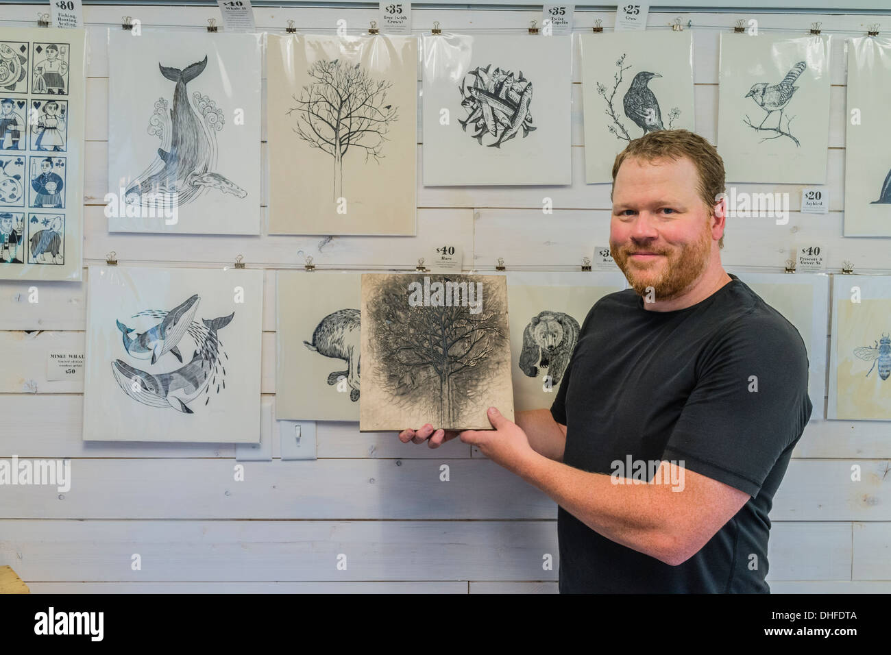 Artist Graham Blair, a woodblock printmaker holds an inked woodblock at his studio in Quidi Vidi in St. John's Newfoundland. - Stock Image