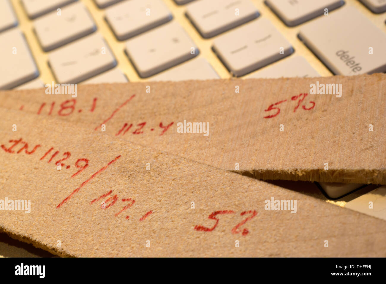 LUMBER HUMIDITY MOISTURE REDUCTION CALCULATIONS OF KILN TIMBER SLICES LAYING ON COMPUTER KEYBOARD - Stock Image